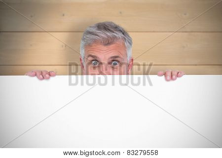 Casual man showing a poster against bleached wooden planks background