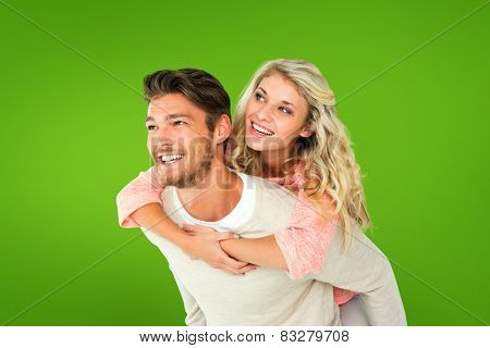 Handsome man giving piggy back to his girlfriend against green vignette