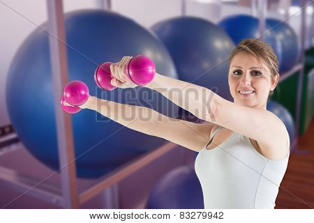 Woman holding weights against exercise balls on rack in studio