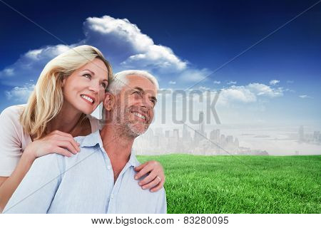 Smiling couple embracing and looking against blue sky over city