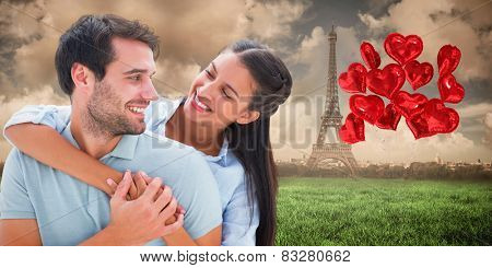 Cute couple smiling at each other against paris under cloudy sky