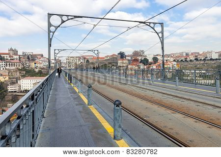 Subway railway tracks and electric cables on the superior deck of the Dom Luis I bridge connecting Vila Nova de Gaia to the city of Porto, seen in the background, over the Douro River