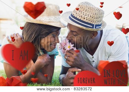 Happy couple lying in garden together smelling flowers against valentines message
