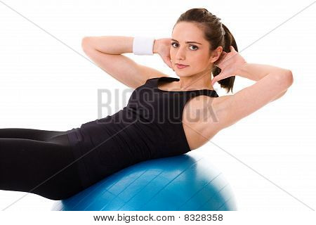 Young Attractive Female Exercise Using Blue Fitness Ball, Isolated