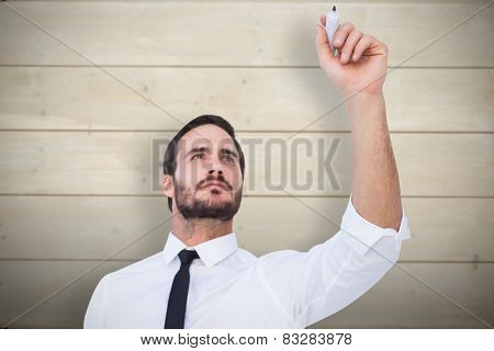 Focused businessman writing with marker against bleached wooden planks background