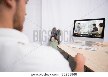 Business people in office at presentation against businessman with legs crossed at ankle on office desk