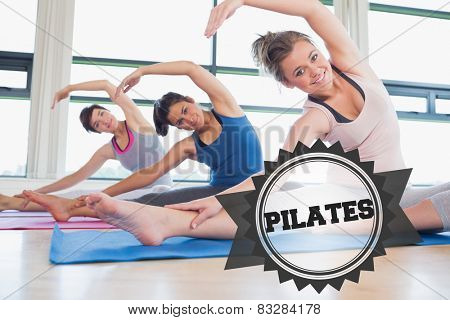 The word pilates and women stretching at yoga class against badge