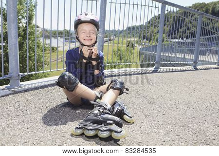 A Little girl in roller skates at a park