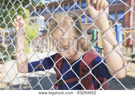 A sad little girl at school playground