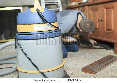 A worker with a vacuum system trying to clean something.
