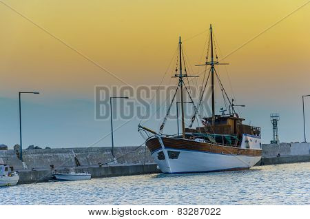 Fishing boat on a harbor at sunset
