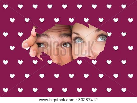 Young couple peeking through torn paper against valentines day pattern