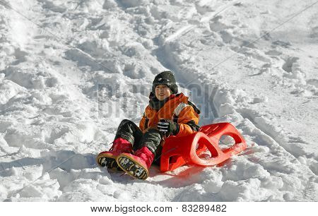 Child Plays With Sled In The Snow