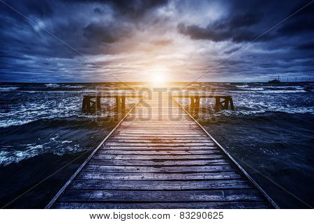 Old wooden jetty during storm on the ocean. Abstract light at the end. Concept of hope, future, religion, god etc.