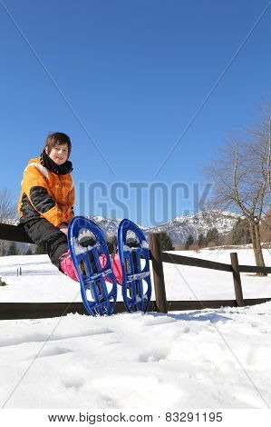 Child With Blue Snowshoes In The Mountains