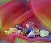 picture of floaties  - A selection of tumbled chakra gemstones laying on floaty rainbow colored chiffon material - JPG