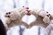 stock photo of knitwear  - Heart shape made of hands wearing knitwear gloves outdoors - JPG