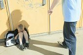stock photo of playground school  - A boy bullying another in school playground - JPG