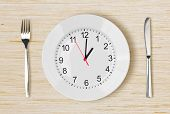 image of clocks  - Dinner plate with clock face on wooden table - JPG