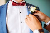 pic of boutonniere  - Pinning a Boutonniere for a groom for wedding - JPG