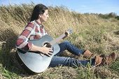 stock photo of thermos  - Country hippie girl with guitar at wheat field drinking black caffee from a mug thermos of relying on the old retro suitcase - JPG