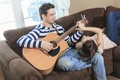 picture of serenade  - A Handsome man serenading his girlfriend with guitar at home in the living room - JPG