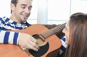 pic of serenade  - A Handsome man serenading his girlfriend with guitar at home in the living room - JPG