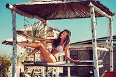 stock photo of sunny beach  - young woman in bikini  sit at shade at seaside beach enjoy in summer hot sunny day - JPG
