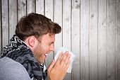 image of blow-up  - Close up side view of man blowing nose against wooden planks - JPG