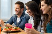 picture of beside  - Happy young friends sitting beside bruschetta served on table - JPG