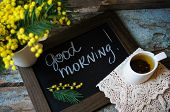 picture of mimosa  - Glass cup with tea and blooming yellow mimosa with good morning note on wooden background - JPG