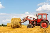 pic of tractor  - Tractor carrying hay at field in summer day - JPG