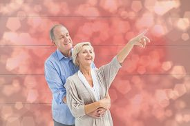 stock photo of male pattern baldness  - Happy mature couple embracing and looking against light glowing dots design pattern - JPG