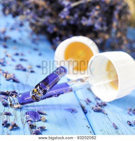 closeup of some pipettes with flower essence and a pile of lavender flowers in the background, on a worn blue wooden surface