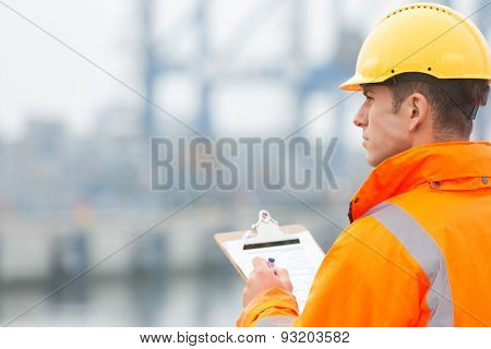 Rear view of mid adult man writing on clipboard in shipping yard