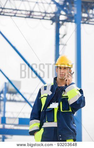 Mid adult male worker using walkie-talkie in shipping yard
