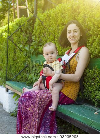 A Young Mother In Eastern Dress, Holding A Small Child In A Baby Carrier Bag.