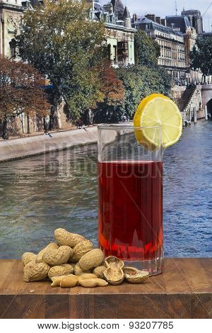 Glass Of Vermouth With Peanuts On A Wood Table