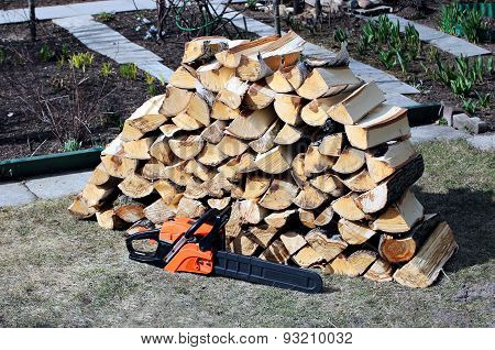 Stabel Of Chopped Birch Wood And A Chainsaw In The Yard