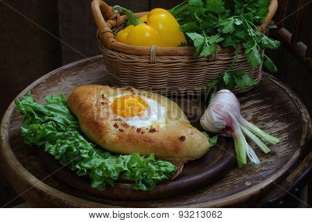 Open Pie With An Egg Submitted On Leaves Of Green Salad