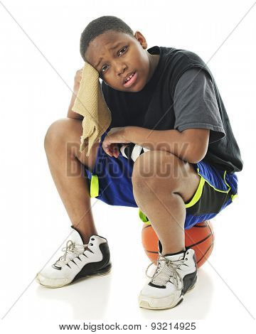 A preteen athlete looking distressed and wiping his brow as he sits on his basketball.  On a white background.