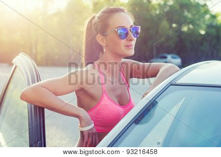 Athlete sporty fit young woman in sports bra wearing sunglasses standing leaning on car with door op