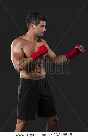 Portrait of a muscular man practicing body combat against a dark background