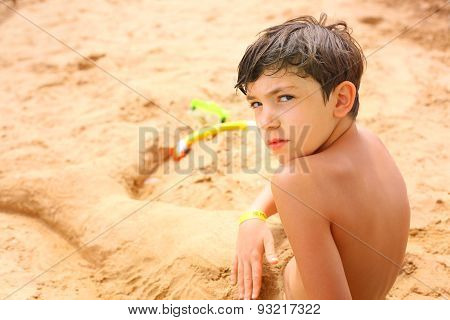 Preteen Handsome Boy In The Sand Sculpture Of Mermaid Tail With Tube And Snorkeling Mask