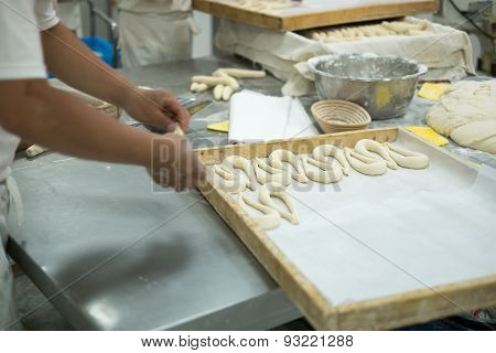 Bakers Making Fresh Pretzels On Dough Covered Table
