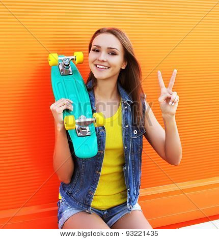 Fashion Portrait Of Hipster Cool Girl In Colorful Clothes With Skateboard Having Fun Against The Ora