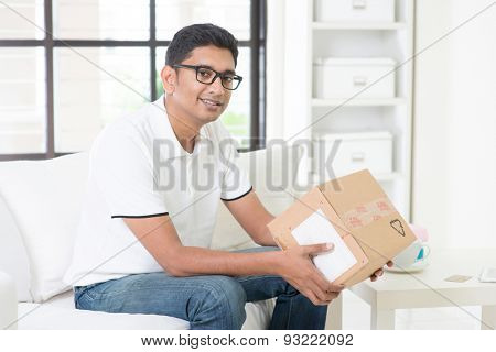 Courier delivery concept. Indian guy received an express parcel and checking the box at home. Handsome male portrait. Asian man sitting on sofa indoor.