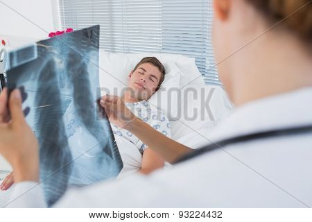 Doctors examining patients xray in hospital room