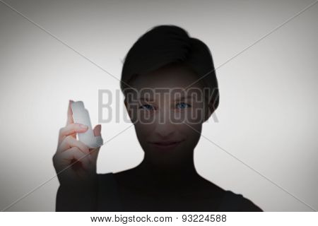 Pretty woman holding inhaler smiling at camera against grey vignette