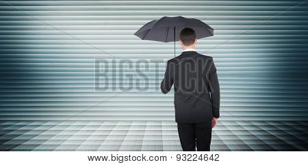 Businessman sheltering under black umbrella against grey shutters